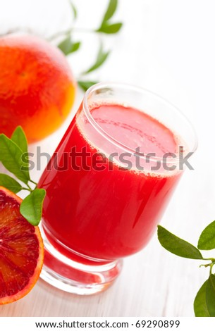 blood orange juice in glass with halved blood orange on the wooden table