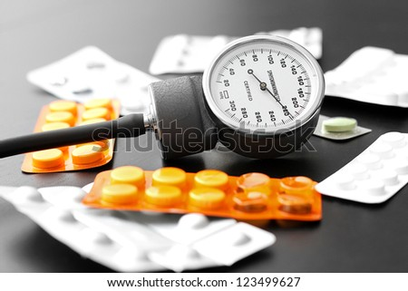 blood pressure instrument and pills on the table