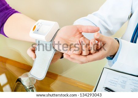Blood pressure measuring. Male doctor check patient pulse in cabinet.