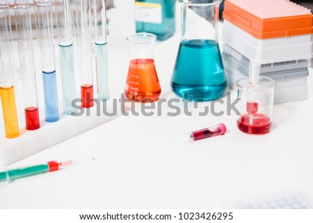 blood sample and syringe. injection and vaccination. drug discovery, pharmacology and biotechnology concept. science and medical research background with copy space.
