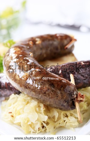 Blood sausage and white pudding with sauerkraut and baked potato