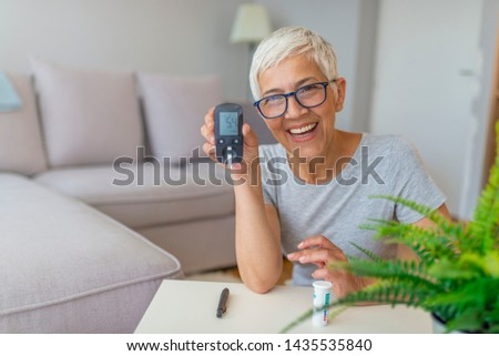 Blood sugar testing at home. Checking Blood Sugar Level At Home. Diabetic Checking Blood Sugar Levels. Woman checking blood sugar level by glucometer and test stripe at home