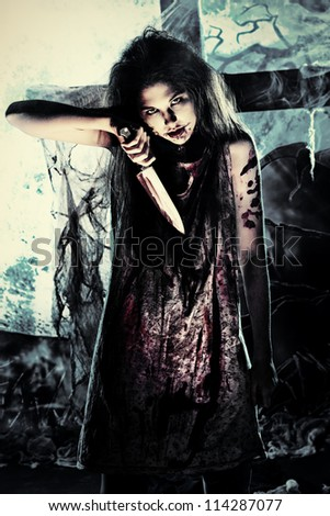 Bloodthirsty zombie with a knife standing at the night cemetery in the mist and moonlight.