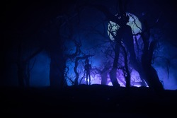 bloodthirsty zombies attacking concept. Silhouette of scary zombie walking in the dead forest at night. Creative table decorations. Selective focus