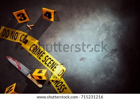 Bloody knife and cigarette stubs at a police crime scene with yellow tape and numbered clues with copy space alongside #715231216