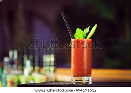 Photo of  Bloody Mary at the bar counter. Classic cocktail. Dark background. Horizontal, lightly toned