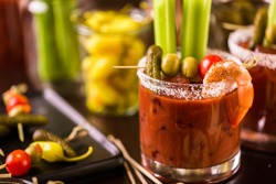 Bloody mary cocktail garnished with celery sticks and olives.