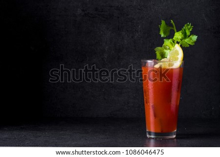 Photo of  Bloody Mary cocktail in glass on black background. Copyspace