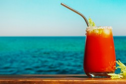Bloody Mary cocktail in salt rimmed glass. Alcohol cocktail made of tomato juice and vodka, decorated celery. Bloody Mary beverage, blue sea on background. Summer resort, beach bar concept.