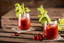 Bloody or virgin mary cocktail served in a cup with celery sticks and cherry tomatoes.