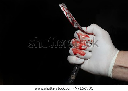 Bloody Razor Against Black Background/Close up of Latex gloved hand holding antique wood handled razor both covered with real blood