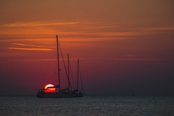 Bloody red sun setting down behind the silohouettes of a two sailboats or yachts moored on an open sea. Adventourous sunset.