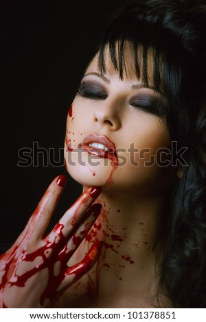 bloody vampire girl with delight on face on a black background