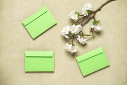 Blooming cherry branch (artificial) and green envelopes flat lay. Spring background. Top view