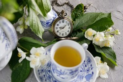 Blooming delicate jasmine flowers and a cup of tonic green tea decorated with a mechanical clock on a chain.