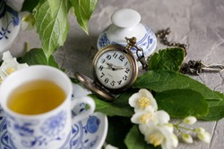 Blooming delicate jasmine flowers and a cup of tonic green tea. Snow-white beautiful flowers.