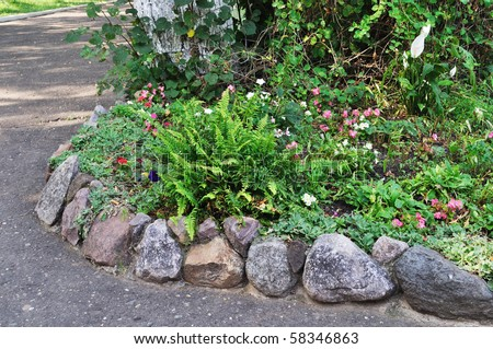 Blooming Flowers In Flower Bed With Stone Border Stock Photo ...