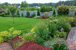 Blooming garden. A flower bed with bright shrubs and trees. Backyard lawn.