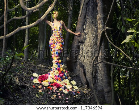Stock Photo Blooming gorgeous lady in a dress of flowers in the rainforest