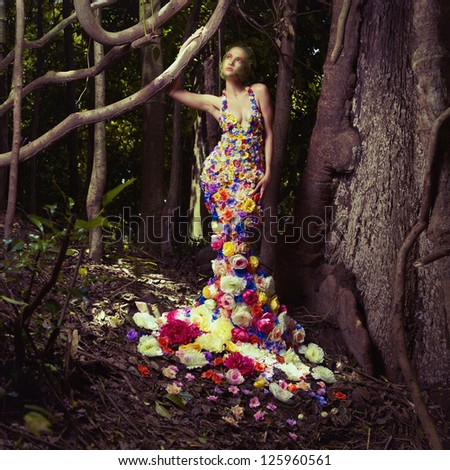 Blooming gorgeous lady in a dress of flowers in the rainforest