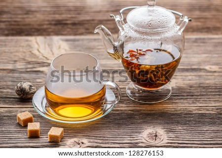 Blooming green tea in glass teapot and cup on a wooden table