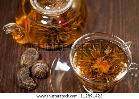 Blooming tea close up in a glass cup on a wooden table