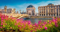 Blooming violet flowers on the shore of Vardar river. Exciting spring cityscape of capital of North Macedonia - Skopje with Archaeological Museum. Colorful view of Art Bridge.