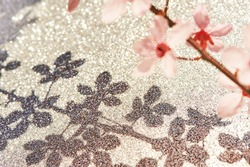 Blossom flowers shadow on glitter surface, shiny background
