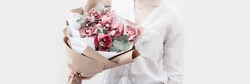 Blossoming delicate flowers of pink orchid in hands of female on light background with copy space. Modern bouquet to gift for your mother or friend.