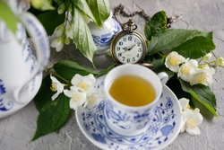 Blossoming tender jasmine flowers and a tea set with a mechanical clock on a chain.