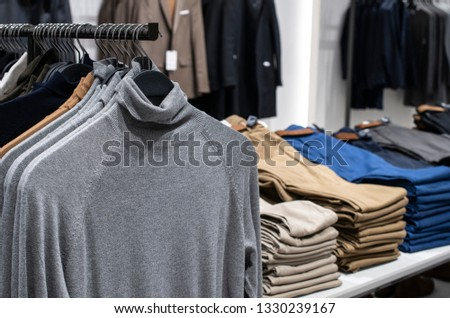 Blouses and jeans on shelf in fashion clothing store. Casual clothes in shop. Commercial and fashion concept.