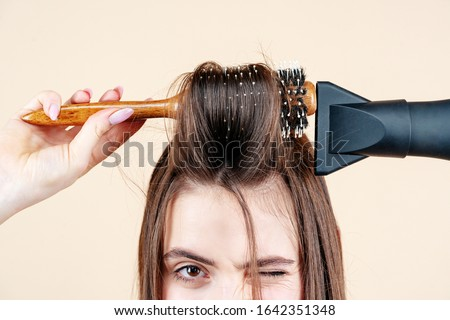 Blow dryer close up. Drying long brown hair with hair dryer and round brush. Hairdresser blow drying her hair. Beautiful girl using a hair dryer close up