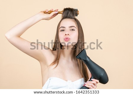 Blow dryer. Drying long brown hair with hair dryer and round brush. Hairdresser blow drying her hair. Beautiful girl using a hair dryer