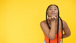 Blow kiss. Sending love. Affection expression. Flirty cute woman showing air smooch gesture isolated on yellow copy space background.