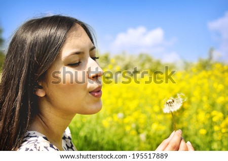 Blowing a dandelion. A beautiful young woman blowing a dandelion.