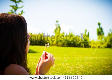 Blowing a Dandelion - Young women blowing a dandelion