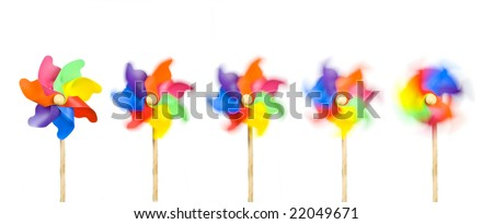 Blowing in the Wind: five toy windmills spinning stationary to fast; isolated on extendable white ground to give good copy-space; high resolution so each image can be used on its own