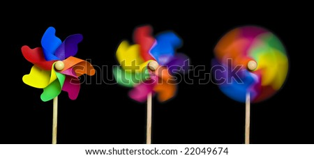 Blowing in the Wind: three toy windmills spinning stationary to fast; isolated on extendable black ground to give good copy-space; high resolution so each image can be used on its own
