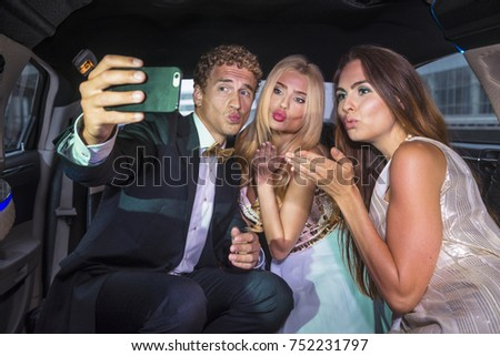 Blowing kisses to the camera in the back of a limousine dressed up for a gala reception