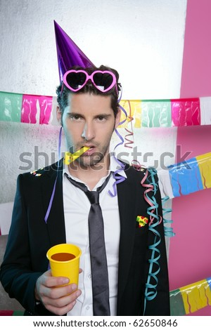 Blowing noisemaker suit party funny gesture young man