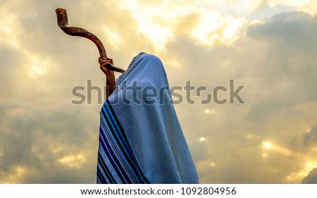 Blowing  the shofar for the Feast of Trumpets - Jewish man in a tallit prayer shawl against dramatic sky