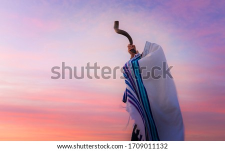 Blowing the shofar for the Feast of Trumpets - Jewish man in a traditional tallit prayer shawl blowing the ram's horn against beautiful sunset sky