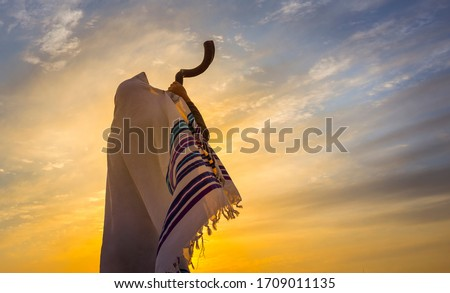 Blowing the shofar for the Feast of Trumpets - Jewish man in a traditional tallit prayer shawl blowing the ram's horn against dramatic sunset sky Foto d'archivio ©