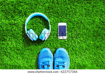 Blue a headphones and white smartphone with sports sneakers shoes on a green grass textured background, top view, flat lay photo