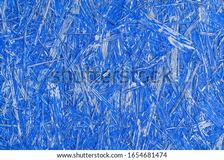 Blue abstract background with wooden texture. Painted OSB panel. detailed view of wood chip particle board building construction material in vivid blue colour.