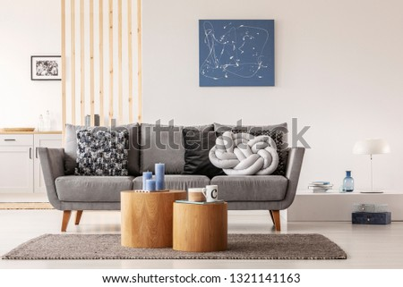 Blue abstract painting on white wall of contemporary living room interior with grey settee with pillows #1321141163
