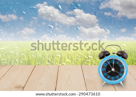 Blue alarm clock on table wood texture with rain drops on a window or water drops on grass blurred with green rice field and blue sky.