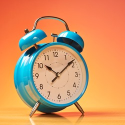 Blue alarm clock on the wooden surface against the orange background