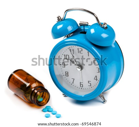 blue alarm clock whith a pill bottle with tablets spilling out