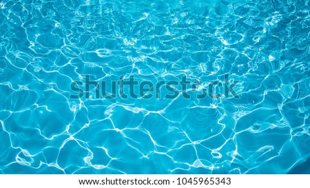 Blue and bright water in swimming pool with sun reflection, Motion of ripple water and gentle wave in pool